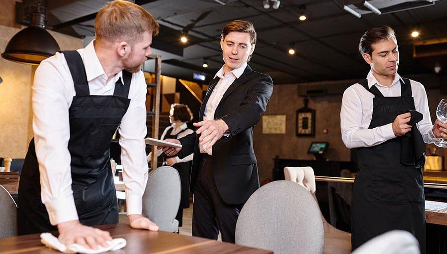 Maitre supervisando al personal de un restaurante